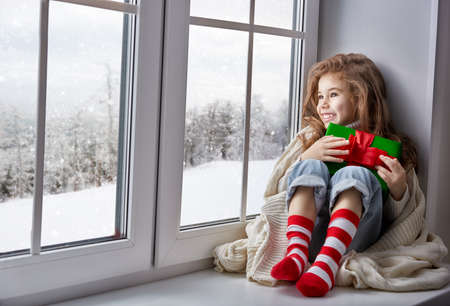 little girl sitting by the window with a gift and looking at the winter forest