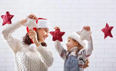 christmas garland: Merry Christmas! Happy mother and daughter hang a Christmas garland.