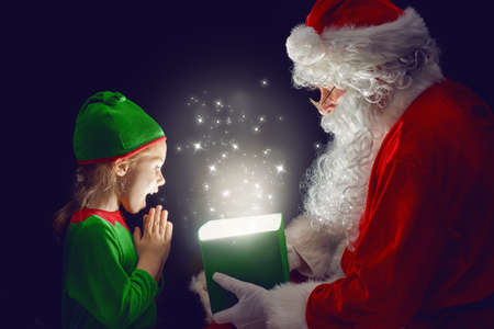 Cute little girl and Santa Claus opening a magic gift box. Stock Photo