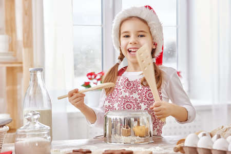 christmas cooking: little girl cooking Christmas biscuits