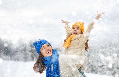madre e hija: ¡Familia feliz! Madre y niña en un paseo de invierno en la naturaleza. Foto de archivo