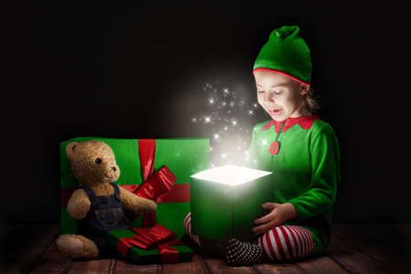 red christmas lights: Cute little girl opening a magic gift box.