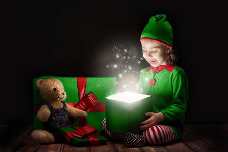 duendes de navidad: Niña linda la apertura de una caja de regalo mágico.