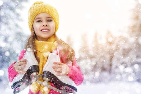cute little girl is going skate outdoors