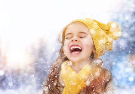 kinder spielen: Happy child girl playing on a winter walk in nature