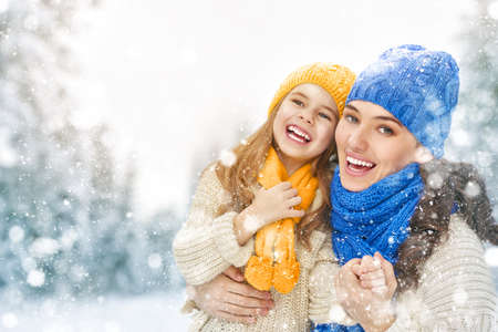 winter: Happy family! Mother and child girl on a winter walk in nature. Stock Photo