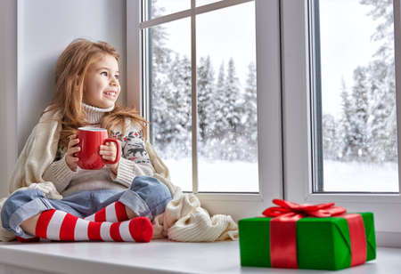 winter holiday: little girl sitting by the window and looking at the winter forest Stock Photo