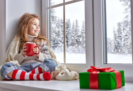 felicidade: menina sentada junto à janela e olhar para a floresta do inverno Imagens