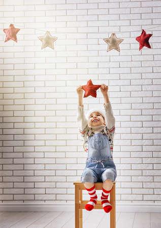 クリスマスイブ!小さな子供は、ガーランドの星をハングアップします。