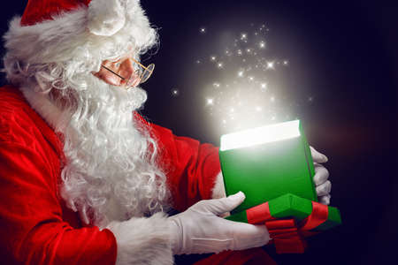 Santa Claus opening a magic gift box.