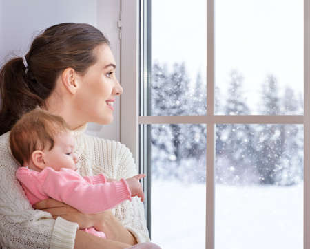 windows: Happy cheerful family. Mother and baby hugging near window. Stock Photo