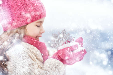 nice face: Happy child girl playing on a winter walk in nature