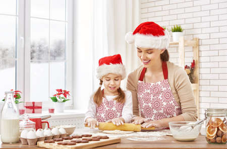 winter window: mother and daughter cooking Christmas biscuits