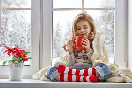 bebes ni�as: ni�a sentada junto a la ventana con una taza de bebida caliente Foto de archivo