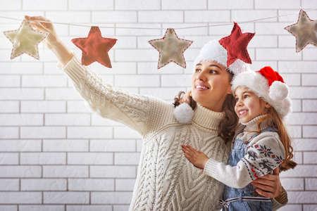 家族: メリー クリスマス!幸せな母と娘は、クリスマスの花輪を掛けます。