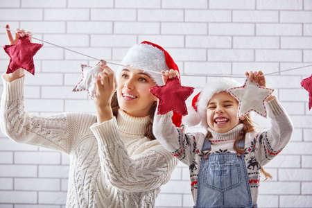mujeres felices: �Feliz Navidad! Madre e hija felices colgar una guirnalda de Navidad.