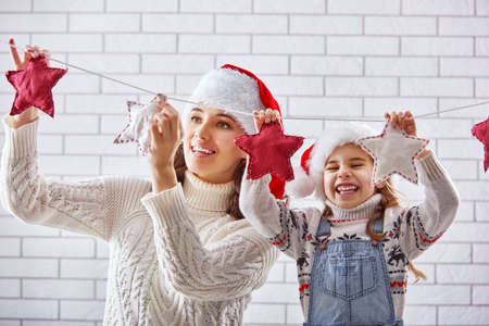 parent child: Merry Christmas! Happy mother and daughter hang a Christmas garland.