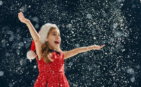 happy little girl: a Christmas miracle! happy little girl catching snowflakes in her hands