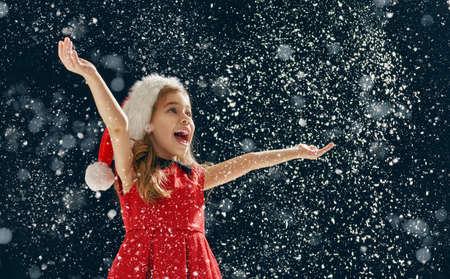 copo de nieve: un milagro de Navidad! Niña feliz captura de copos de nieve en sus manos