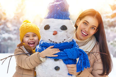 snow woman: Happy family! Mother and child girl on a winter walk in nature. Stock Photo