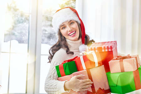 holiday background: Beautiful young woman with gift boxes