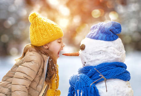 child portrait: Happy child girl playing with a snowman on a winter walk in nature Stock Photo