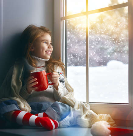 caliente: ni�a sentada junto a la ventana con una taza de bebida caliente y mirando el bosque de invierno