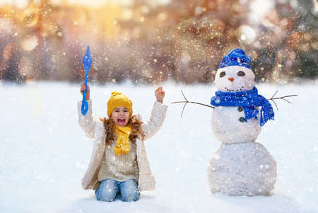 cute babies: Happy child girl playing with a snowman on a winter walk in nature Stock Photo