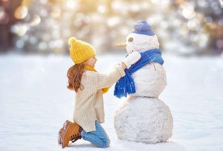 diciembre: Muchacha feliz del niño que juega con un muñeco de nieve en un paseo de invierno en la naturaleza