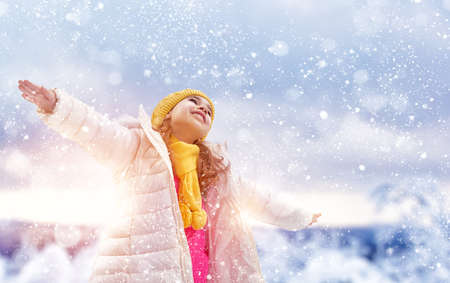 winter fashion: Happy child girl playing on a winter walk in nature