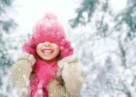 invierno: Muchacha feliz del niño que juega en un paseo de invierno en la naturaleza