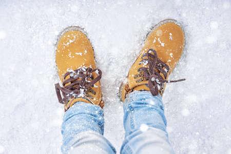caminar: un pie en la nieve. detalle de zapatos de invierno.