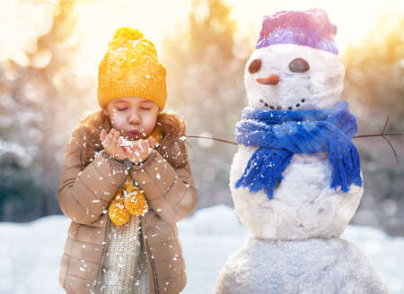 one little girl: happy child girl plaing with a snowman on a snowy winter walk