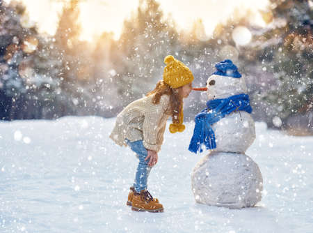 frosty the snowman: happy child girl plaing with a snowman on a snowy winter walk