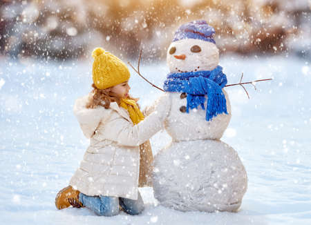 bonhomme de neige: Bonne fille de l'enfant plaing avec un bonhomme de neige sur une promenade d'hiver enneig�e