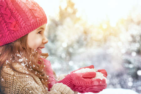 child smile: happy child girl plaing on a snowy winter walk Stock Photo