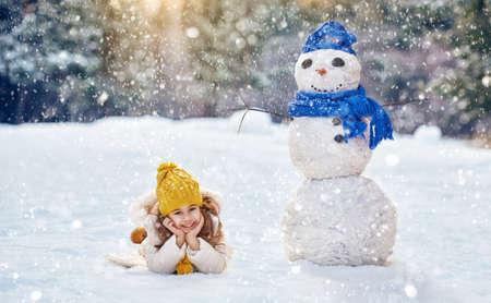 ni�as peque�as: Muchacha feliz del ni�o que juega con un mu�eco de nieve en un paseo de invierno en la naturaleza