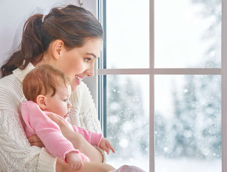 snow woman: Happy cheerful family. Mother and baby hugging near window. Stock Photo
