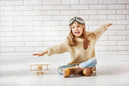 gelukkig kind meisje spelen met speelgoed vliegtuig. de droom om een pilot-
