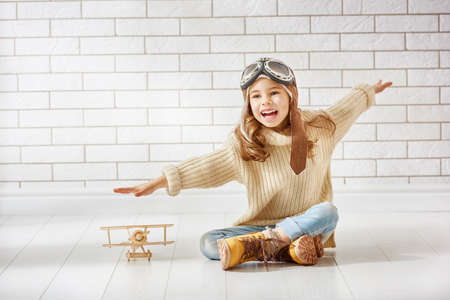 pilot helmet: happy child girl playing with toy airplane. the dream of becoming a pilot Stock Photo