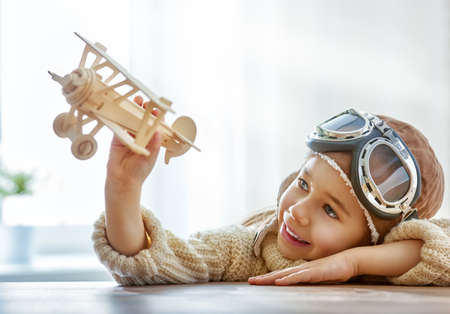 wooden toy: happy child girl playing with toy airplane. the dream of becoming a pilot Stock Photo