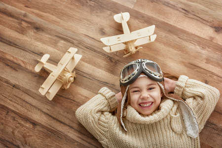 happy child girl playing with toy airplane. the dream of becoming a pilot Stok Fotoğraf