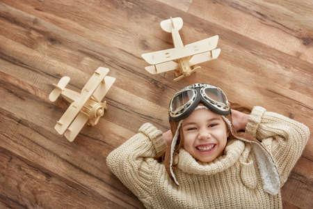 juguetes de madera: niña feliz niño jugando con avión de juguete. el sueño de convertirse en un piloto Foto de archivo