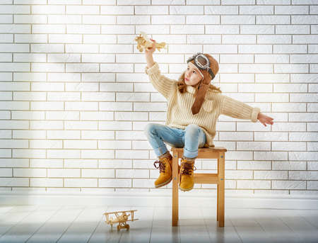 pilot wings: happy child girl playing with toy airplane. the dream of becoming a pilot Stock Photo