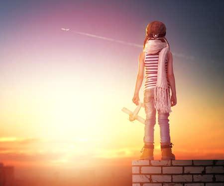een kind speelt met een stuk speelgoed vliegtuig in de zonsondergang en droomt ervan om een pilot-