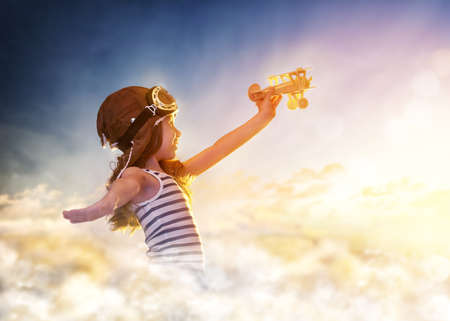 flight helmet: dreams of flight! child playing with toy airplane against the sky at sunset Stock Photo