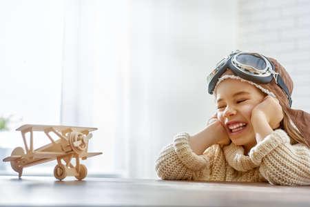 Niña feliz niño jugando con avión de juguete. el sueño de convertirse en un piloto Foto de archivo - 49276266