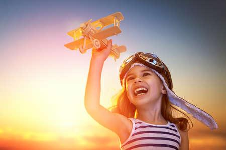 flucht: Träume von Flug! Kind spielt mit Spielzeug-Flugzeug gegen den Himmel bei Sonnenuntergang