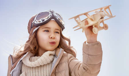 happy child girl playing with toy airplane. the dream of becoming a pilot Archivio Fotografico