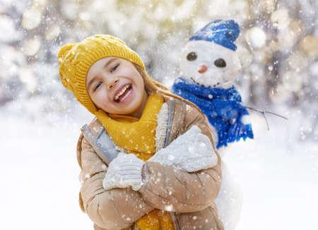 caras: ni�a feliz ni�o plaing con un mu�eco de nieve en un paseo de invierno cubierto de nieve
